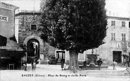 La place du bourg : au premier plan, à côté de la fontaine, l'arbre de la liberté (peuplier d'Italie) symbolisant la révolution française de 1789 ; à gauche, une porte fortifiée vestige de l'enceinte médiévale.